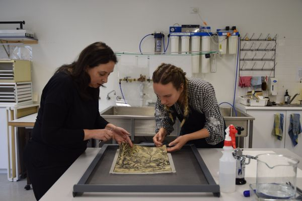 Student conservator Laura Daenke washes the woodblock print The Knight and the lansquenetc from the Baillieu Library Print Collection