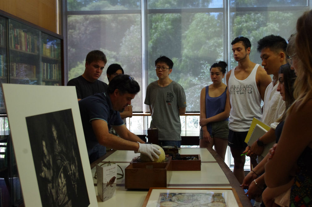Students viewing material from the Plotting the island exhibition